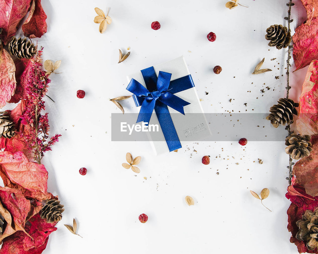 indoors, decoration, christmas, celebration, high angle view, shape, star shape, directly above, holiday, still life, white color, table, christmas decoration, ribbon, no people, ribbon - sewing item, red, geometric shape, circle, christmas ornament