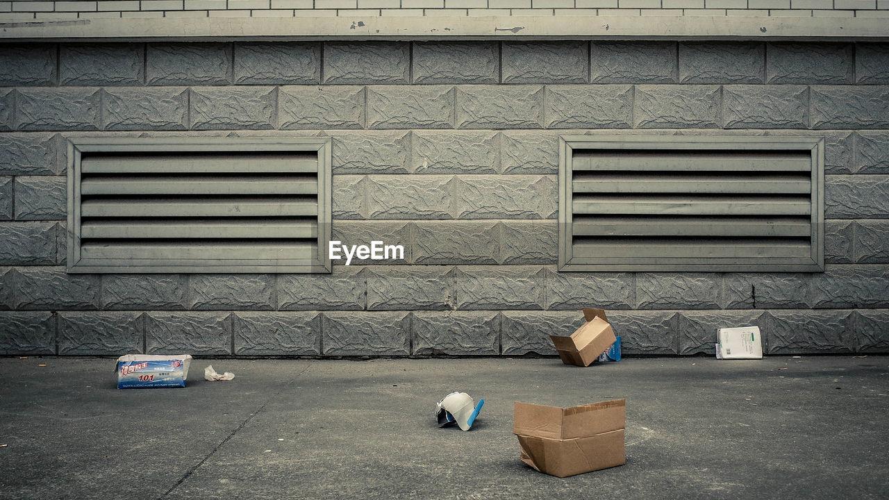 Messy cardboard boxes on sidewalk against brick wall