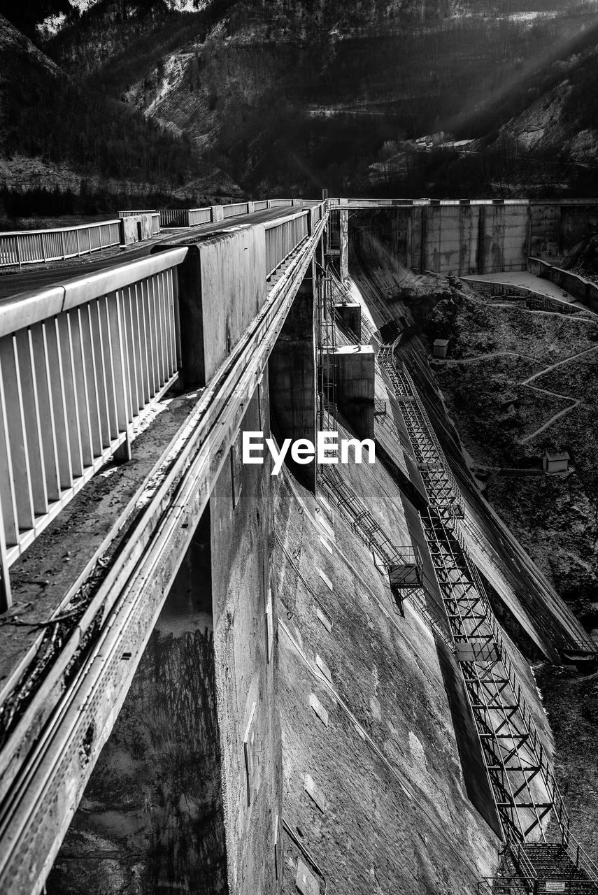 water, built structure, wood - material, no people, architecture, connection, nature, dam, bridge, day, railing, bridge - man made structure, river, high angle view, hydroelectric power, mountain, tree, transportation, outdoors