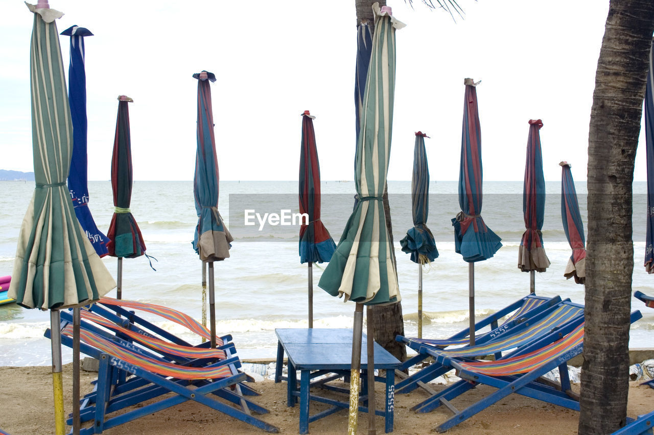 sea, water, beach, sky, chair, land, no people, absence, parasol, seat, horizon over water, nature, table, horizon, scenics - nature, day, in a row, umbrella, beauty in nature, outdoors