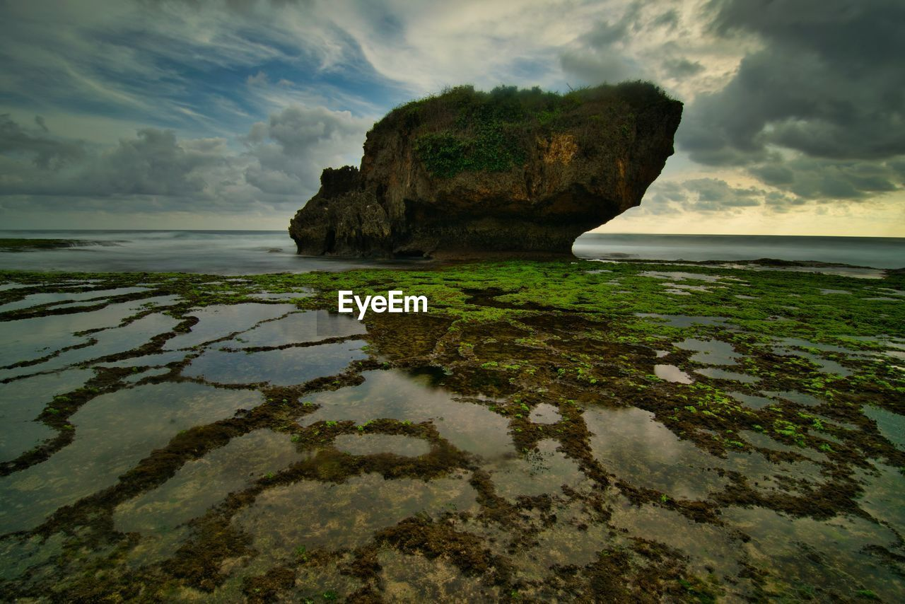 water, cloud - sky, sky, sea, rock, beauty in nature, tranquility, nature, scenics - nature, land, tranquil scene, rock - object, solid, no people, beach, day, outdoors, rock formation, reflection, stack rock