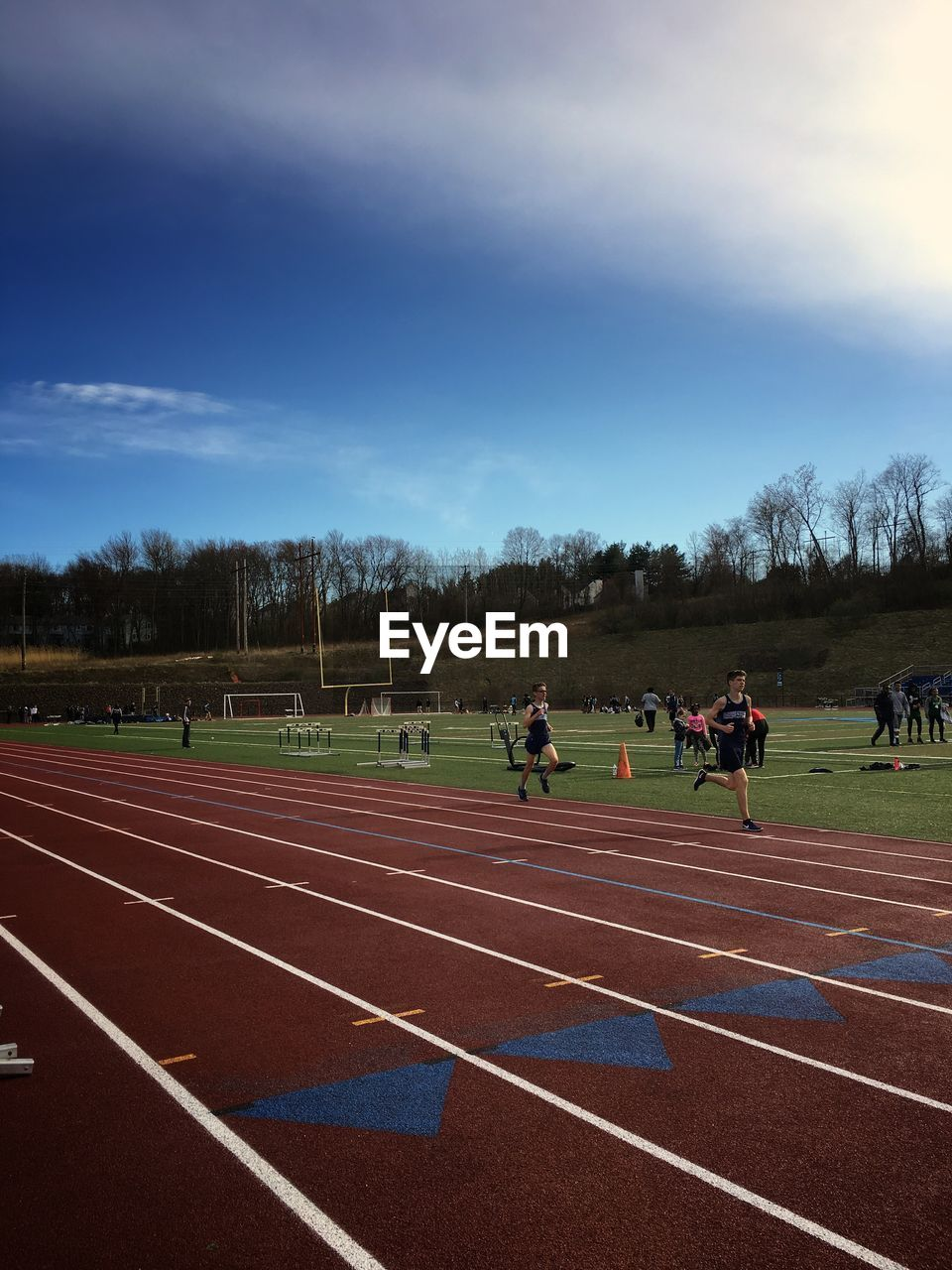 sport, track and field, running track, sky, cloud - sky, nature, sports track, group of people, real people, day, people, competition, men, plant, lifestyles, outdoors, field, tree, grass, competitive sport
