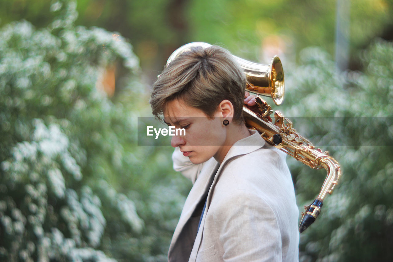 Side View Of Young Woman With Saxophone Standing At Park