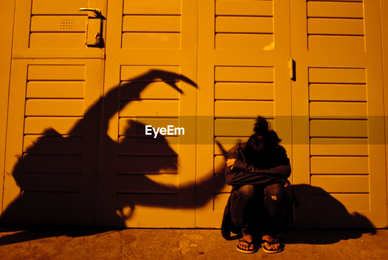 Optical Illusion Of Shadow Reaching Depressed Woman Crouching Against Closed Door
