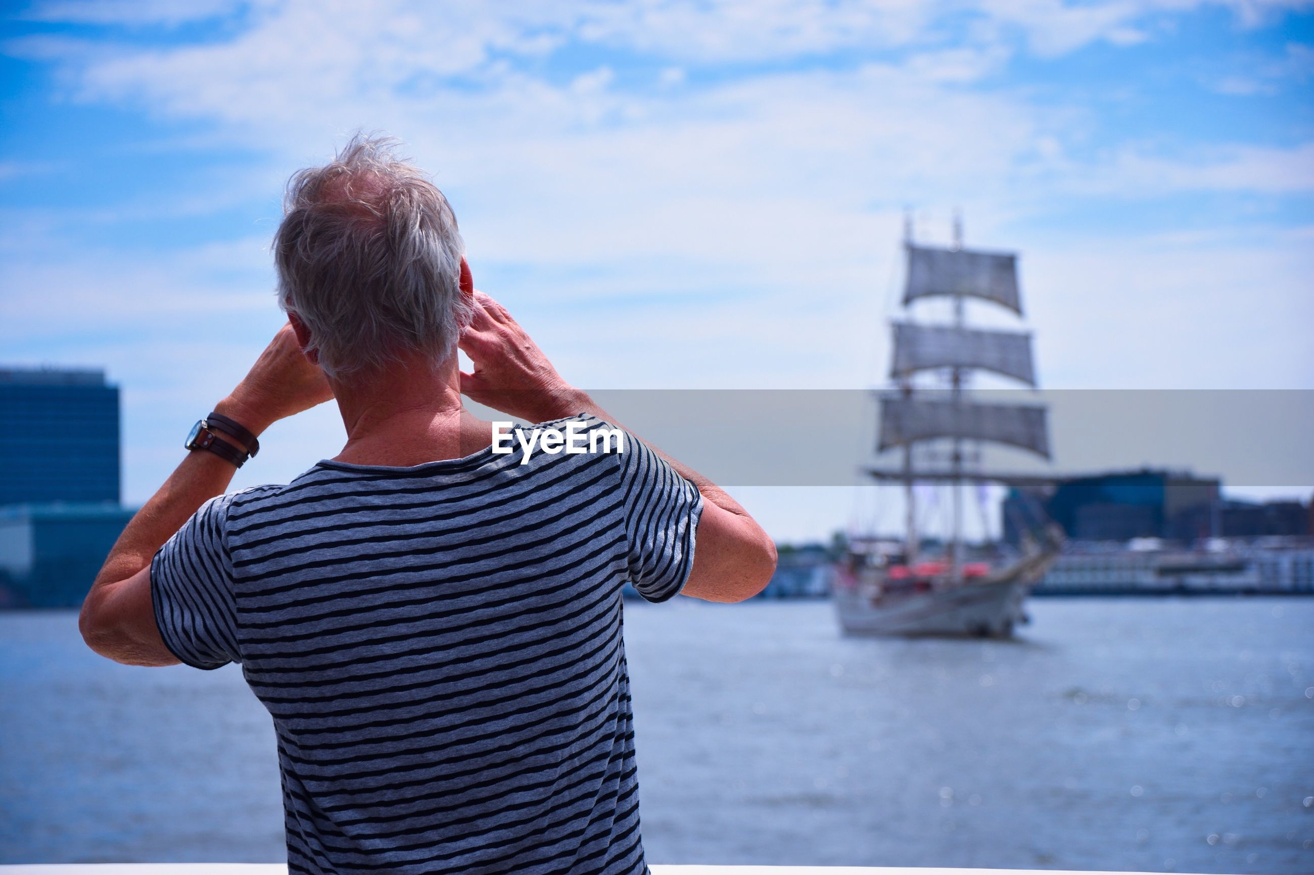 Rear View Of Man Standing In Harbor Against Sky