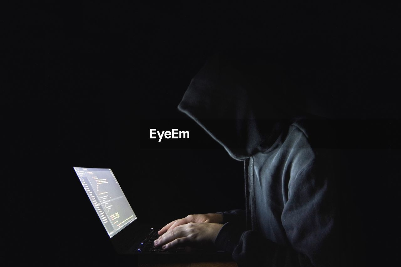 Side view of computer hacker wearing hooded shirt while using laptop against black background