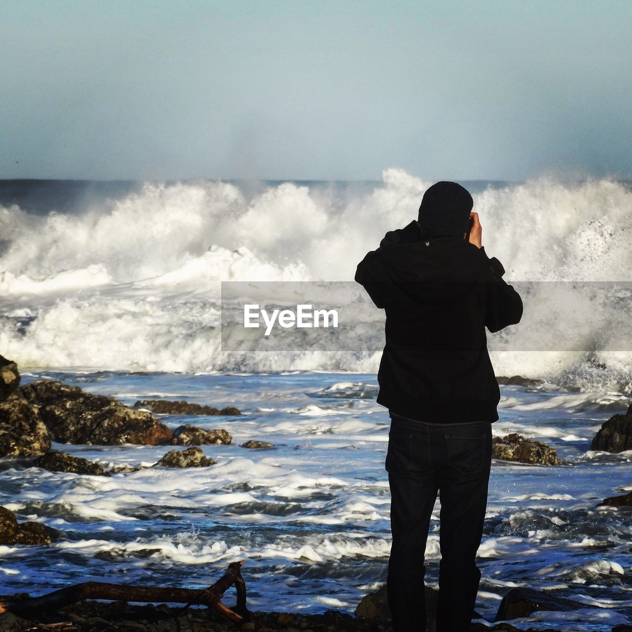 Rear View Of Man Photographing Waves Rushing Towards Shore