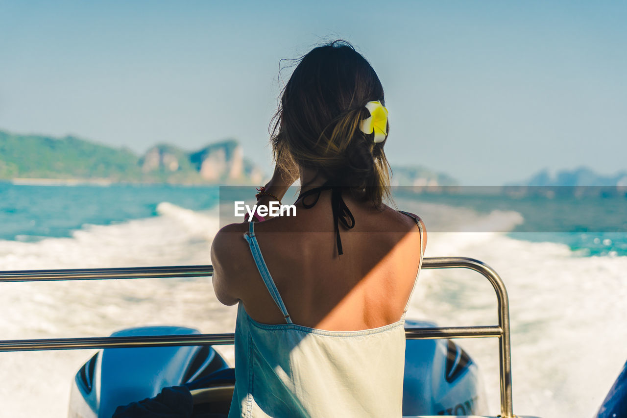 Rear view of woman looking at sea against sky