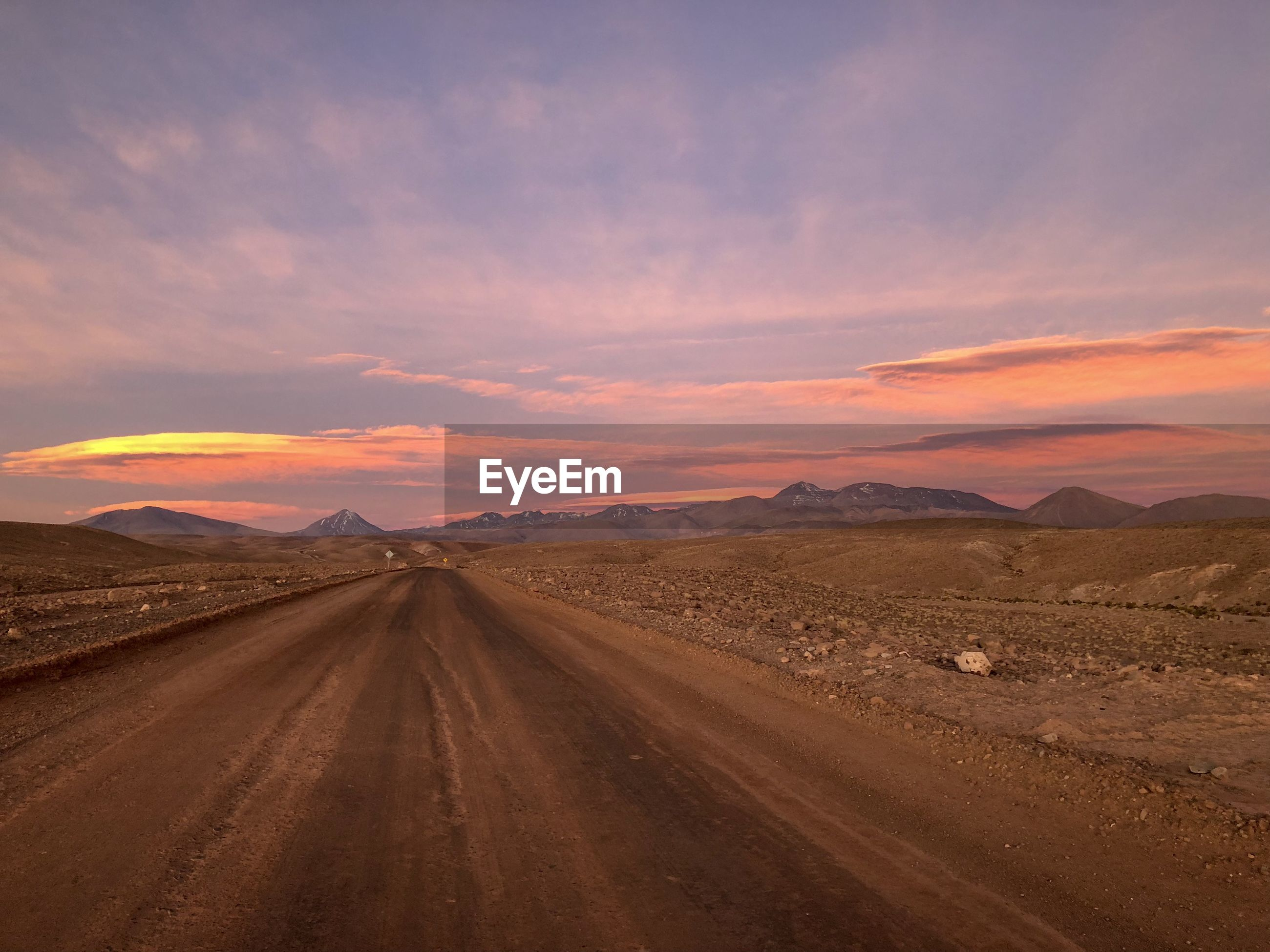 Road amidst desert against sky during sunset