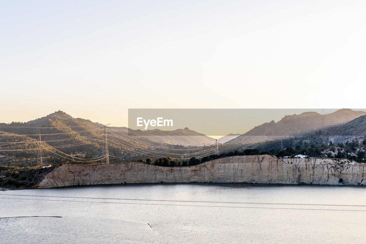 SCENIC VIEW OF LAKE AGAINST MOUNTAINS AGAINST CLEAR SKY