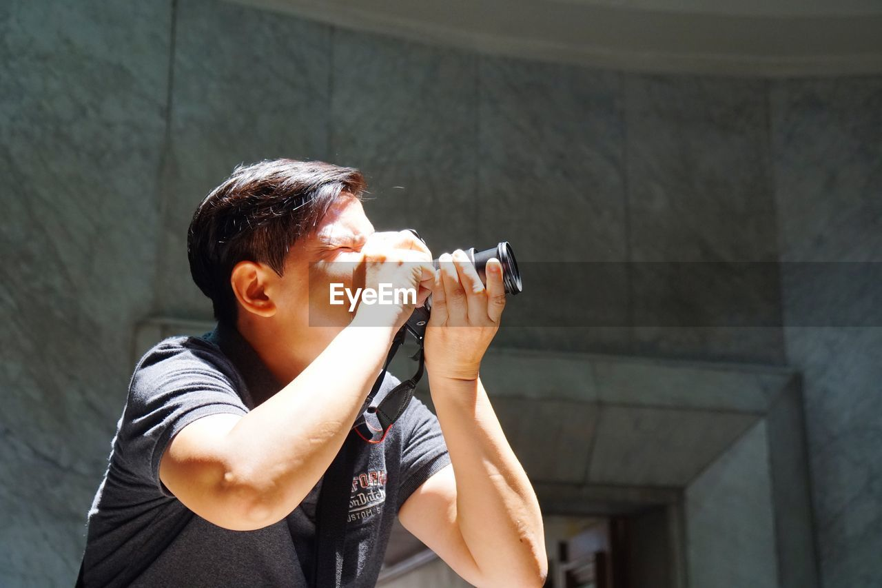 Man photographing through camera against wall