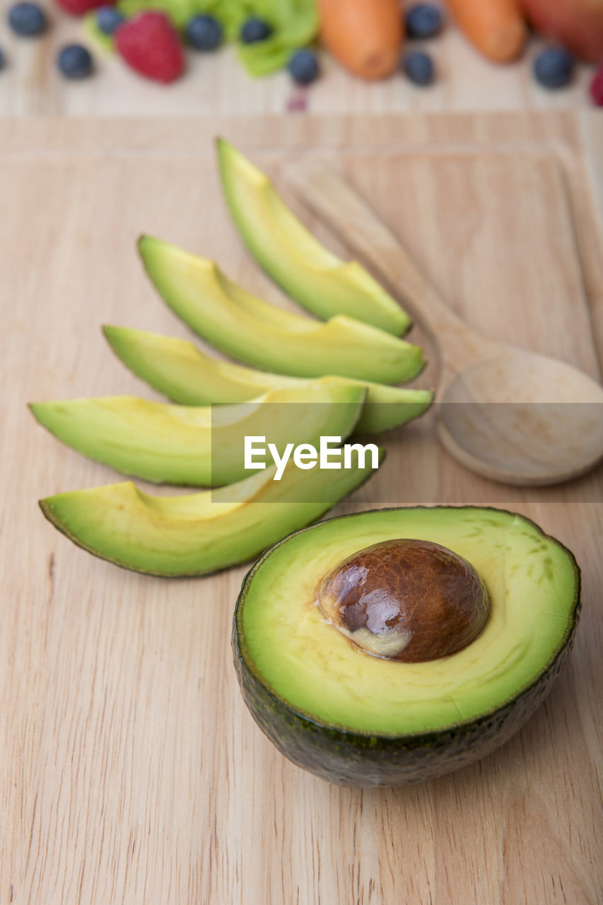High angle view of avocado with wooden spoon on table