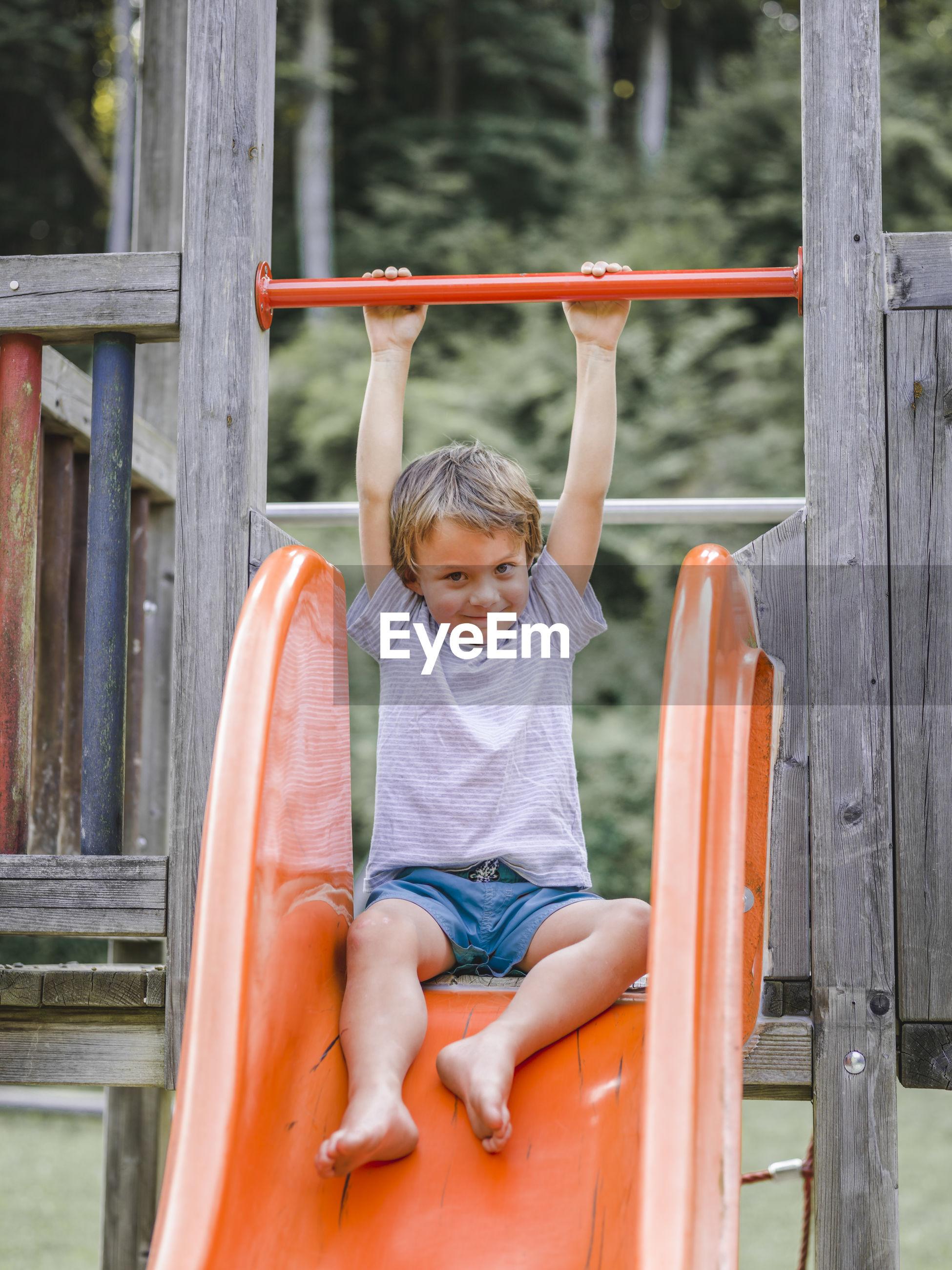 Portrait of smiling boy sliding at playground