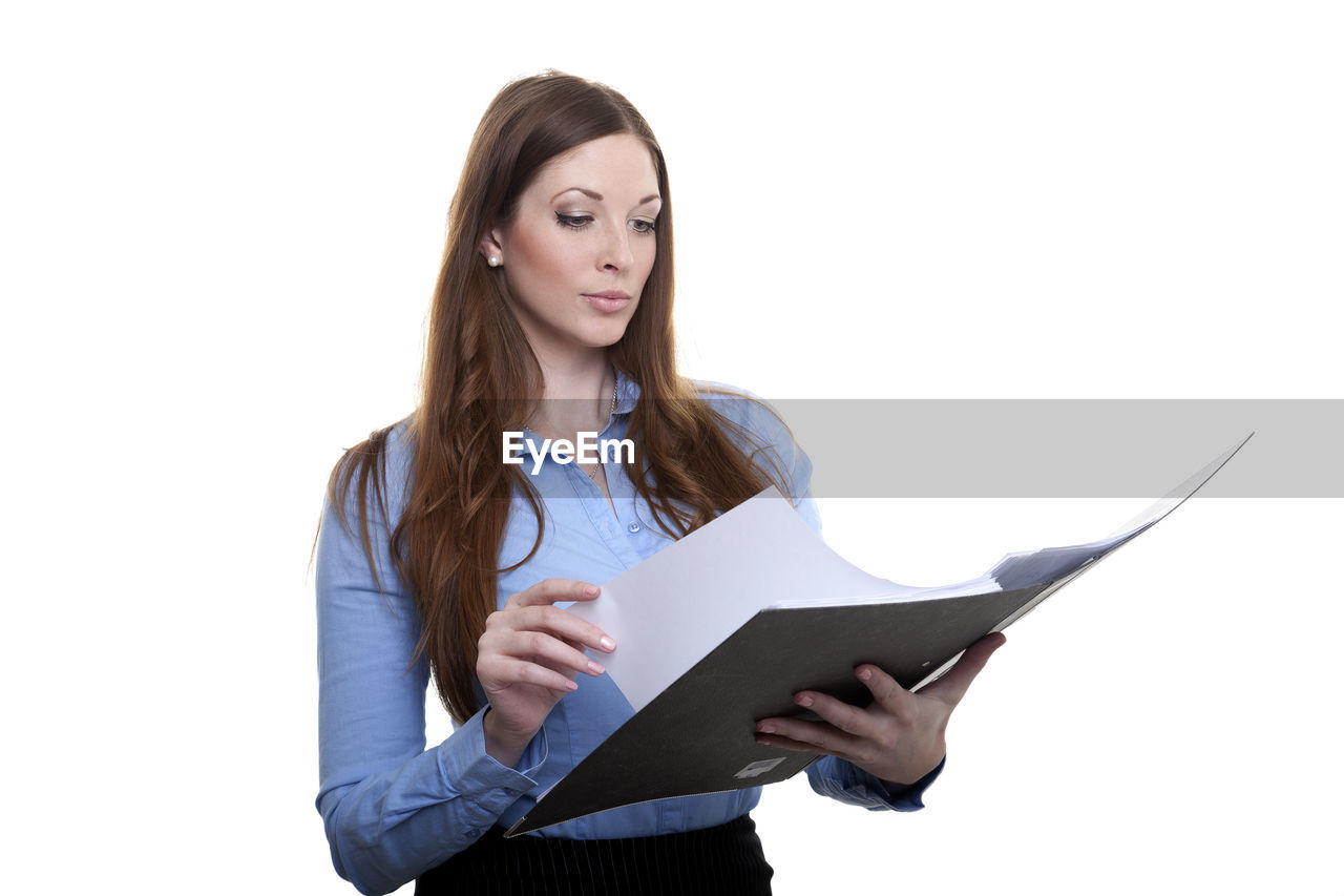 Businesswoman Reading Document Against White Background