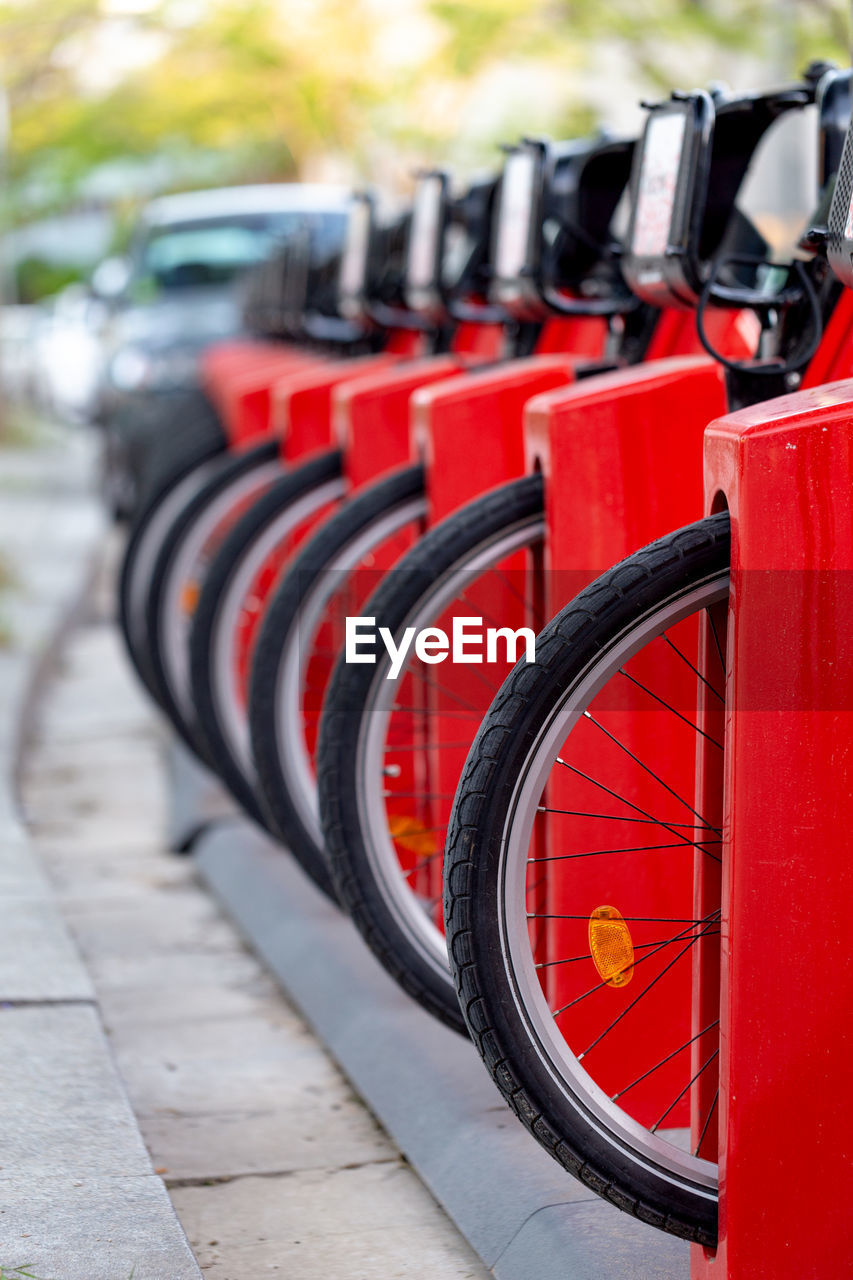 in a row, red, transportation, wheel, focus on foreground, day, mode of transportation, no people, land vehicle, bicycle, order, outdoors, side by side, selective focus, sport, arrangement, repetition, stationary, large group of objects, tire