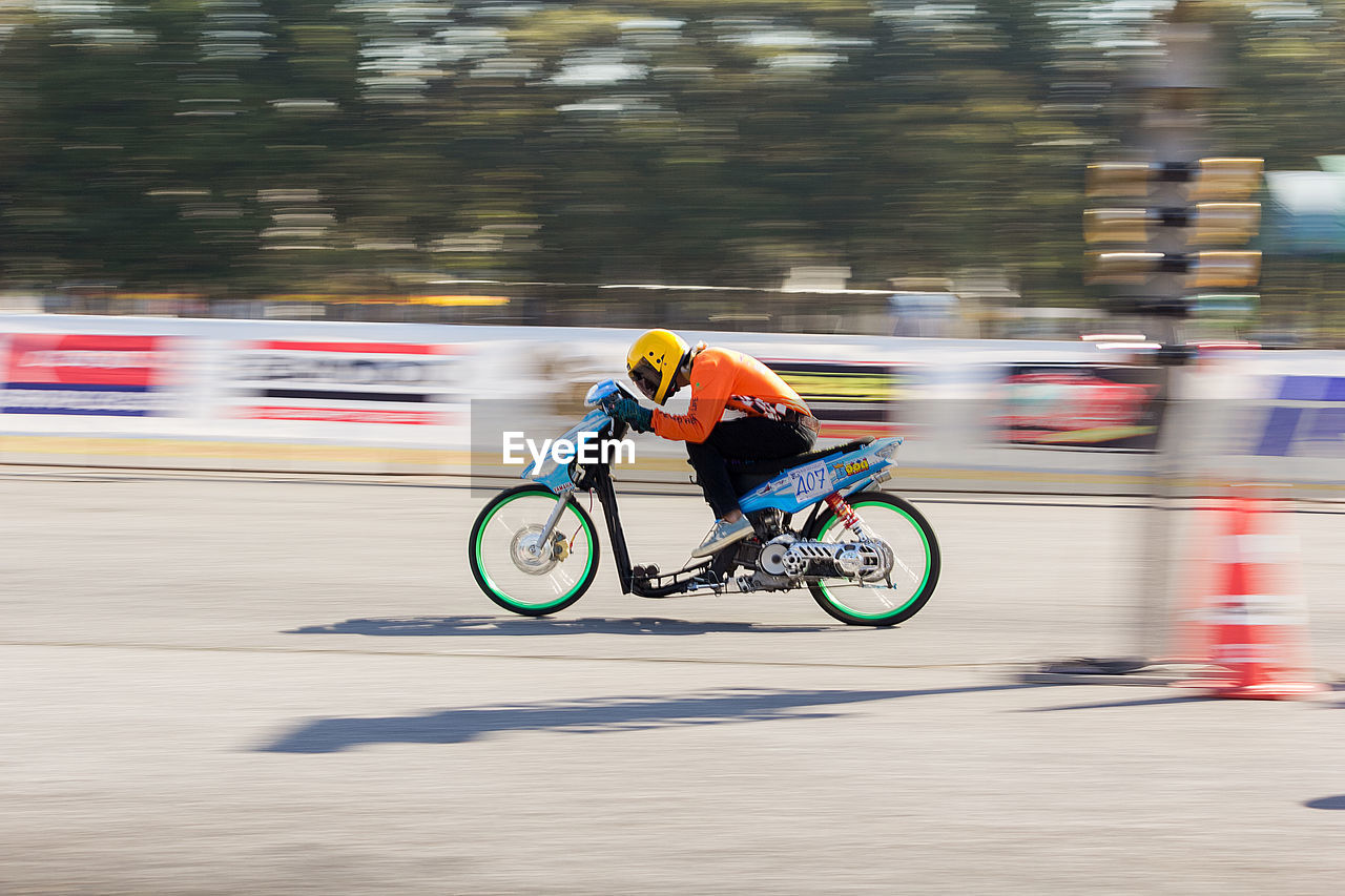motion, blurred motion, speed, transportation, mode of transportation, real people, sport, men, lifestyles, bicycle, activity, ride, riding, competition, one person, day, on the move, side view, land vehicle, skill