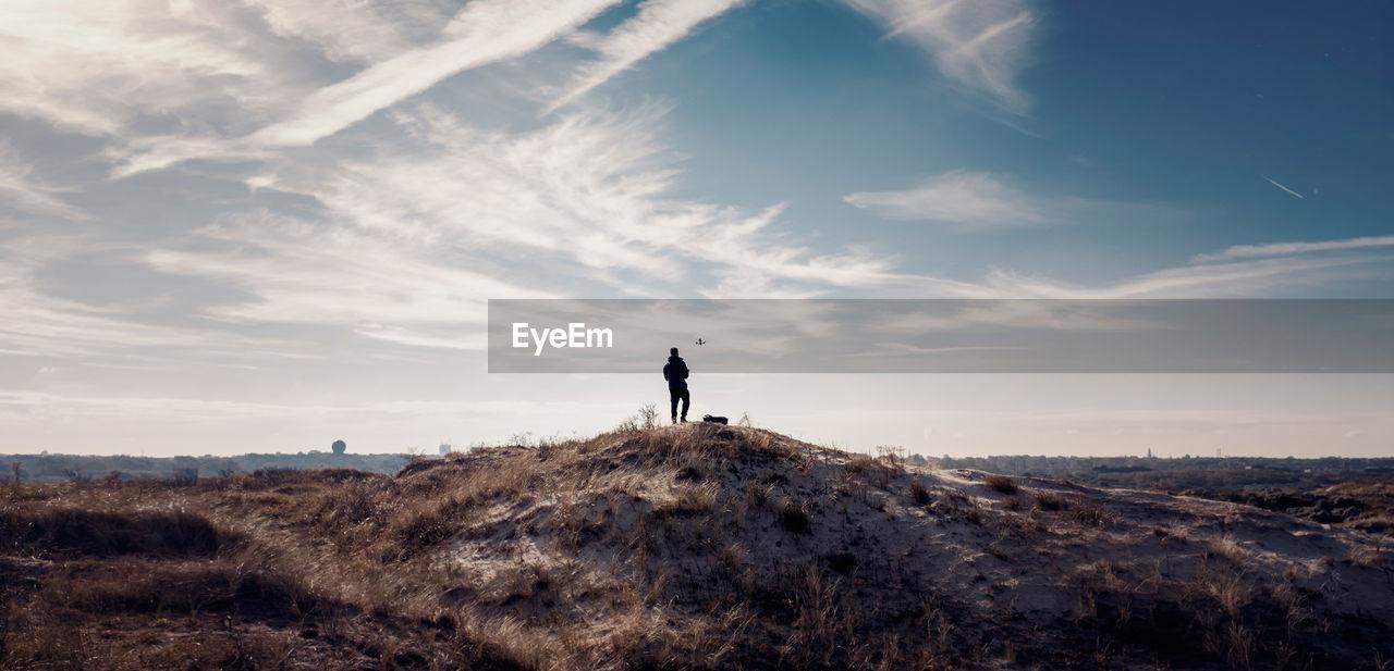 Man On Landscape Against Sky