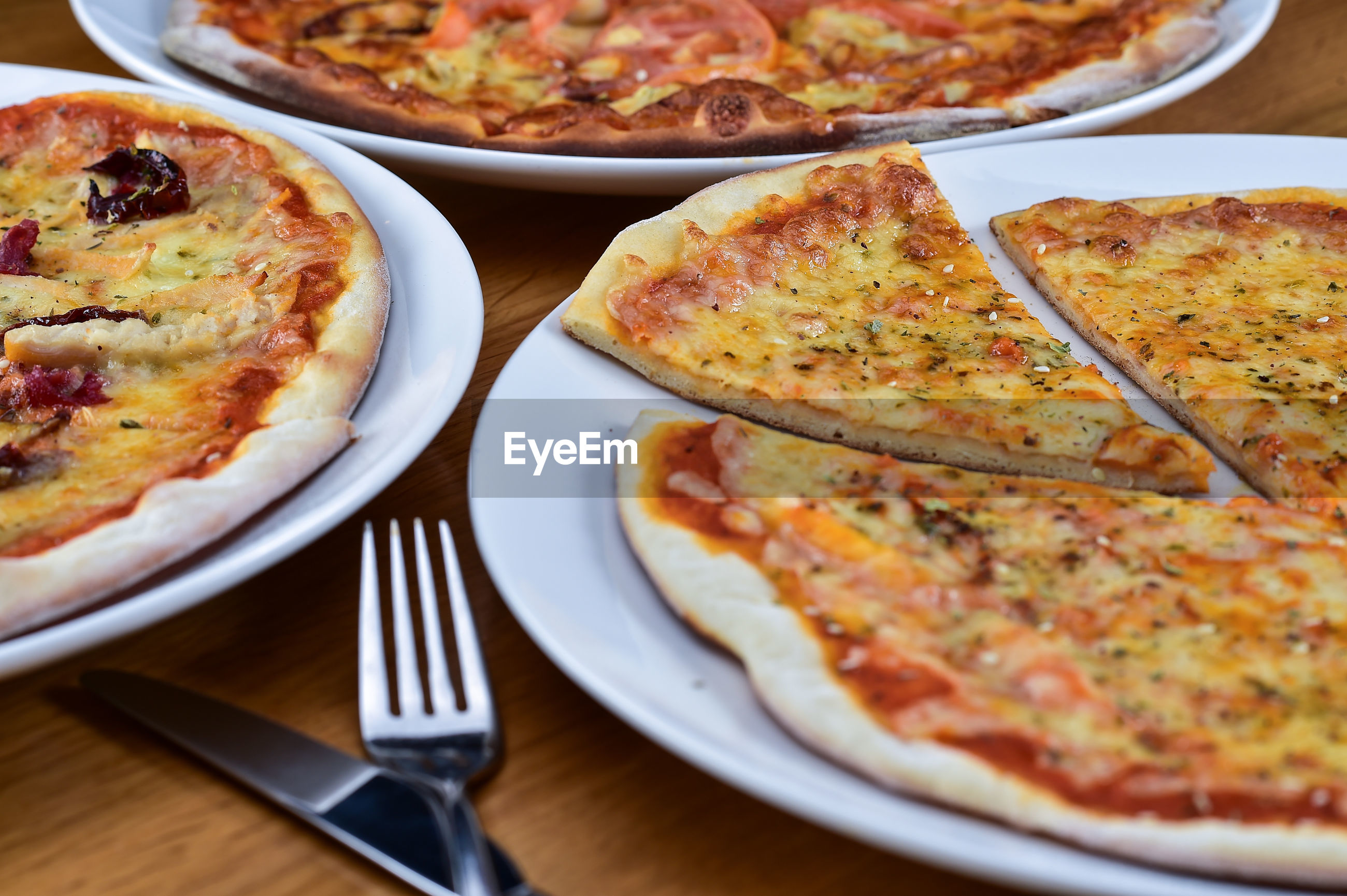 High angle view of various pizza in plates on table