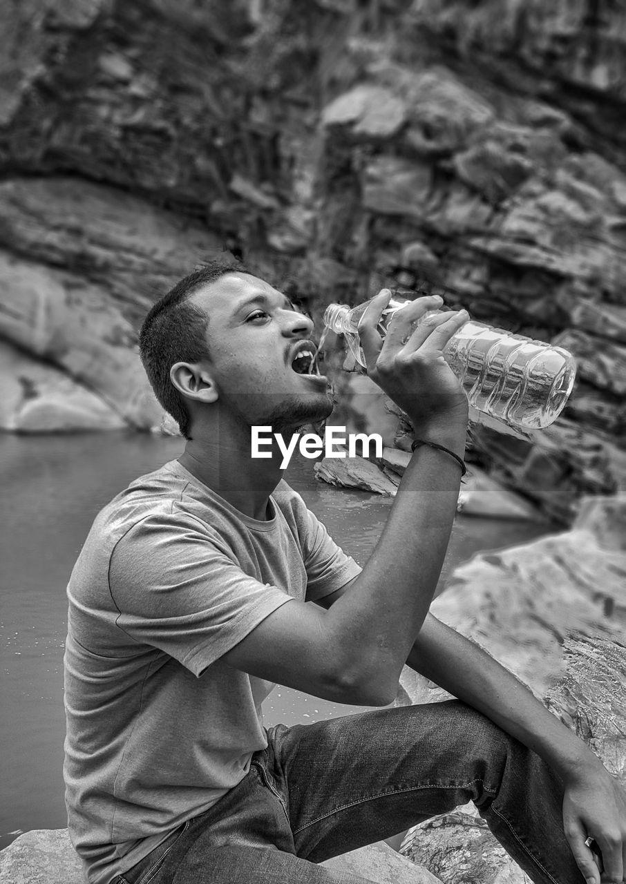 Man Drinking Water While Sitting On Rock At Riverbank