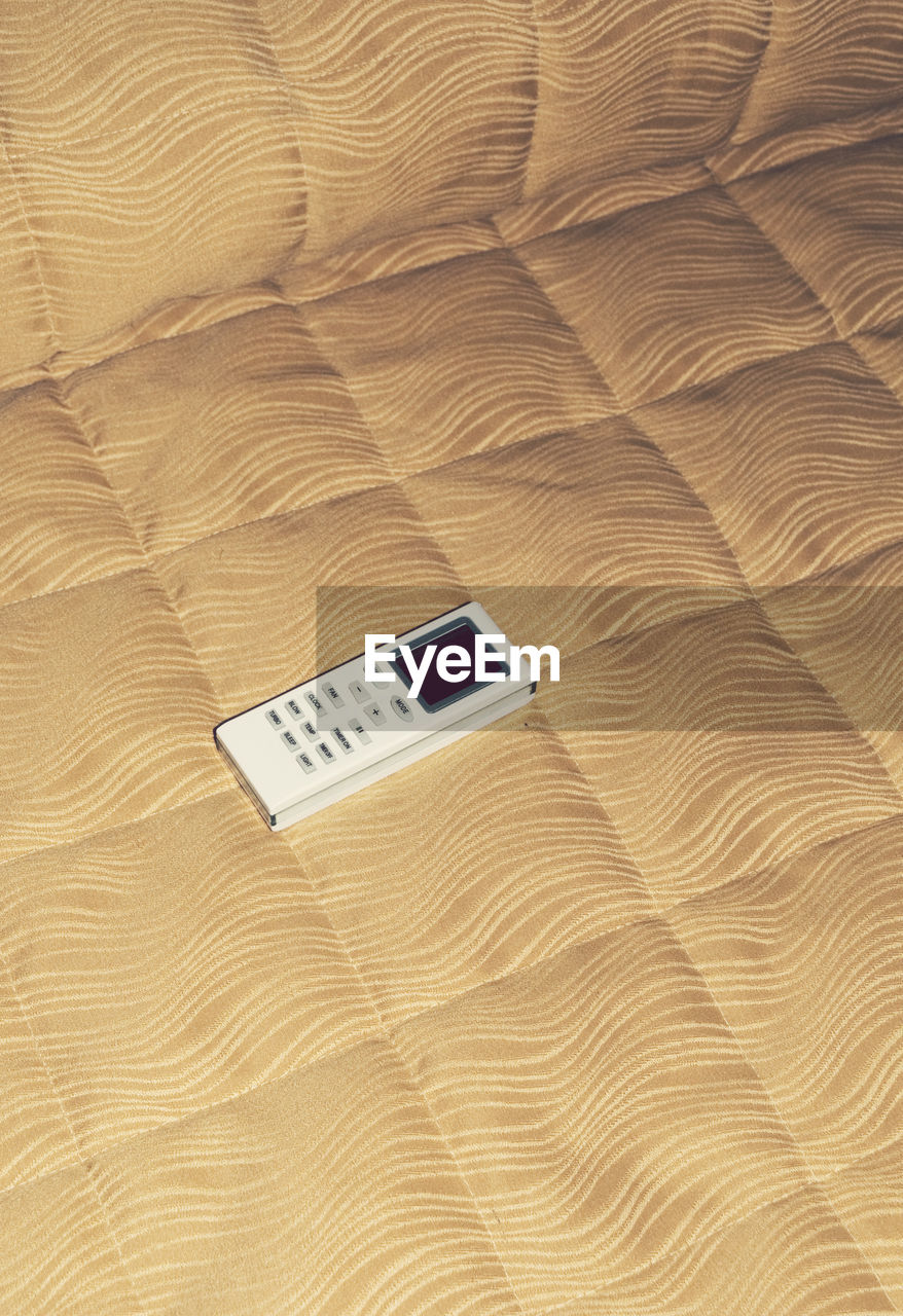 High Angle View Of Air Conditioner Remote On Bed At Home