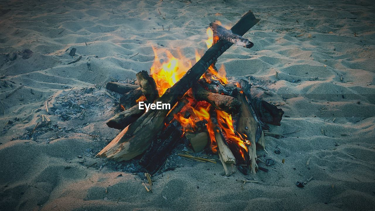 heat - temperature, burning, fire, fire - natural phenomenon, flame, nature, high angle view, bonfire, land, firewood, sand, glowing, beach, orange color, log, wood - material, no people, wood, outdoors, environment, campfire