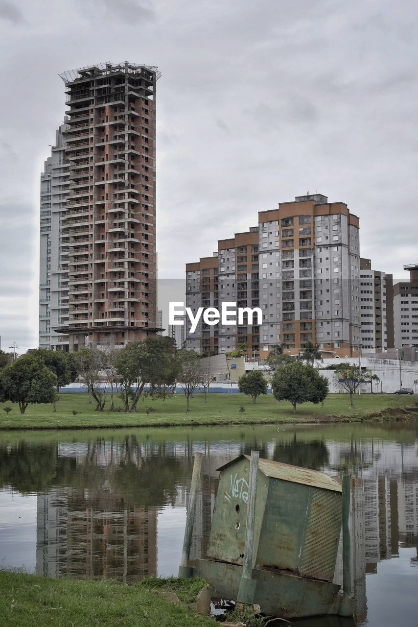architecture, built structure, building exterior, building, sky, reflection, water, city, no people, nature, cloud - sky, plant, day, outdoors, lake, waterfront, tree, residential district, skyscraper, apartment
