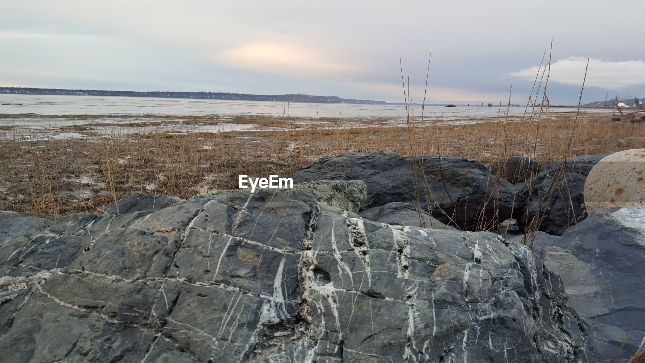 Rocks at beach against sky during winter