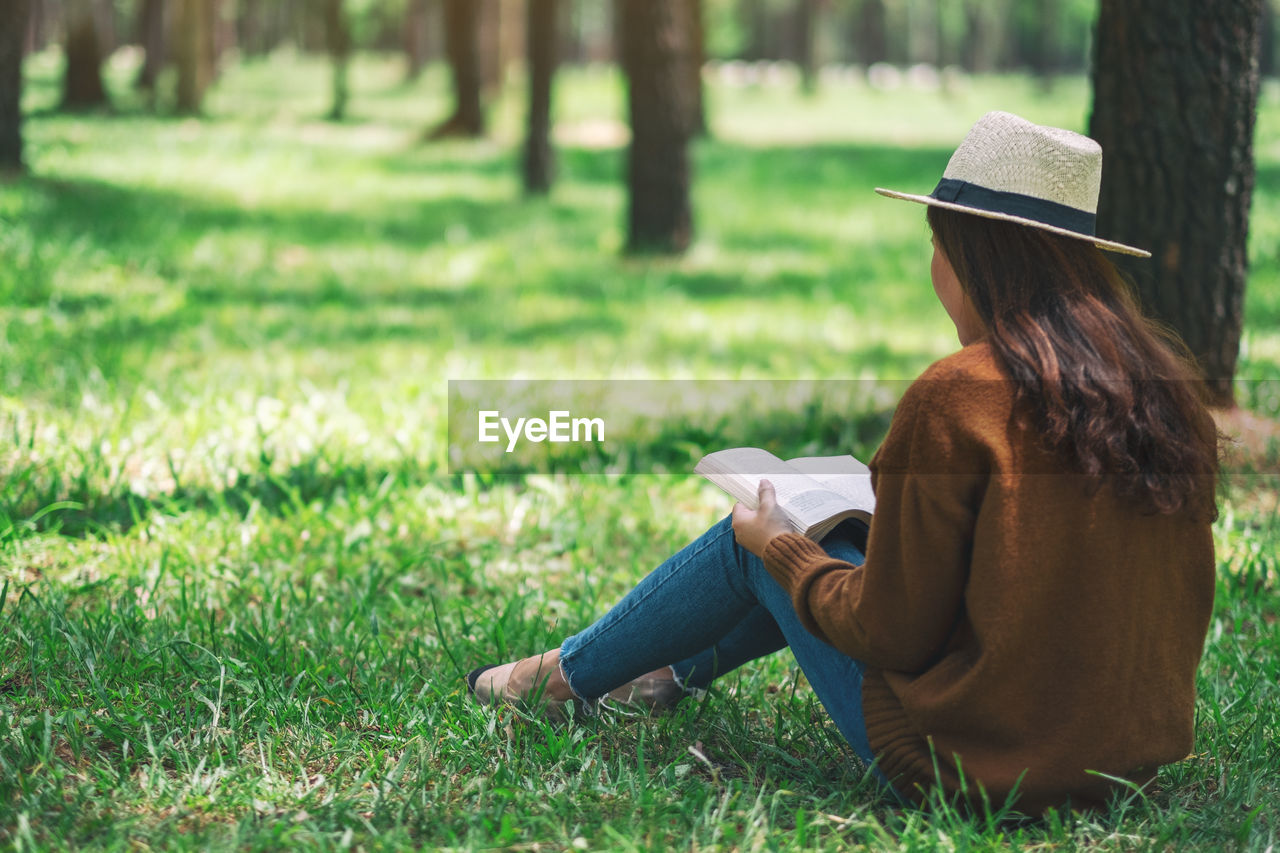 one person, grass, sitting, real people, land, rear view, leisure activity, women, plant, adult, field, hat, lifestyles, green color, clothing, day, nature, long hair, hairstyle, hair, outdoors
