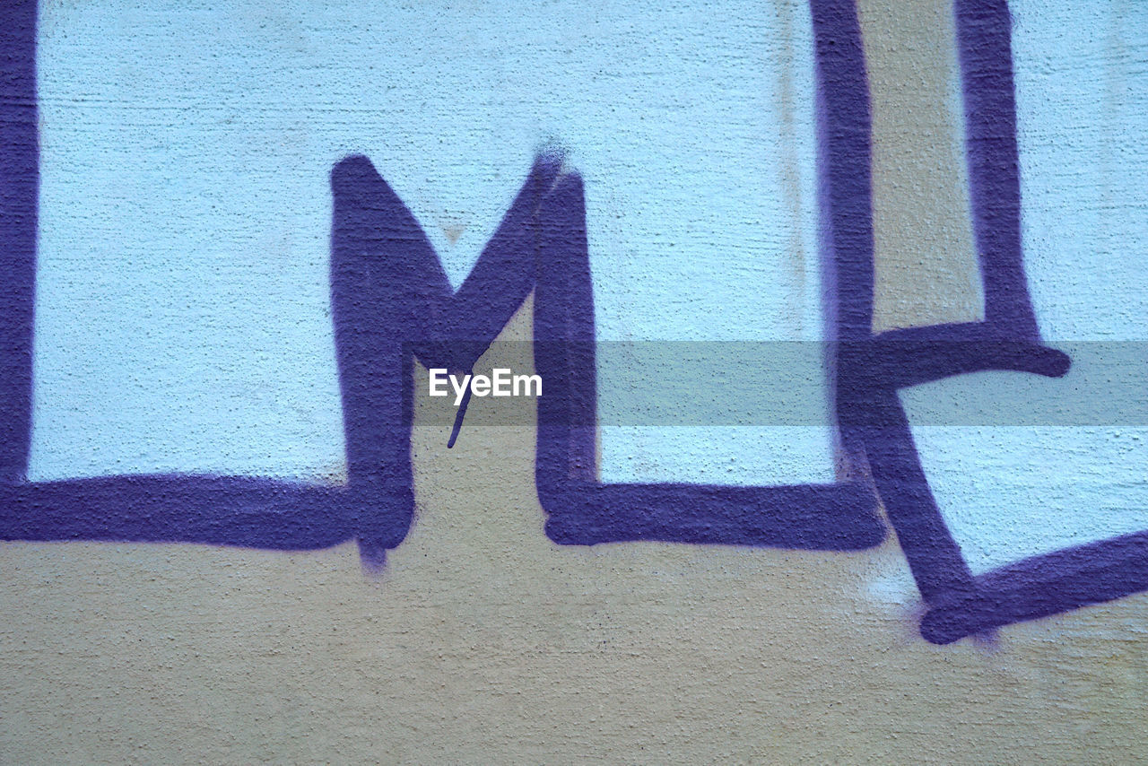 communication, sign, day, creativity, graffiti, art and craft, wall - building feature, architecture, representation, no people, shadow, built structure, blue, outdoors, human representation, guidance, city, text, wall, arrow symbol, message