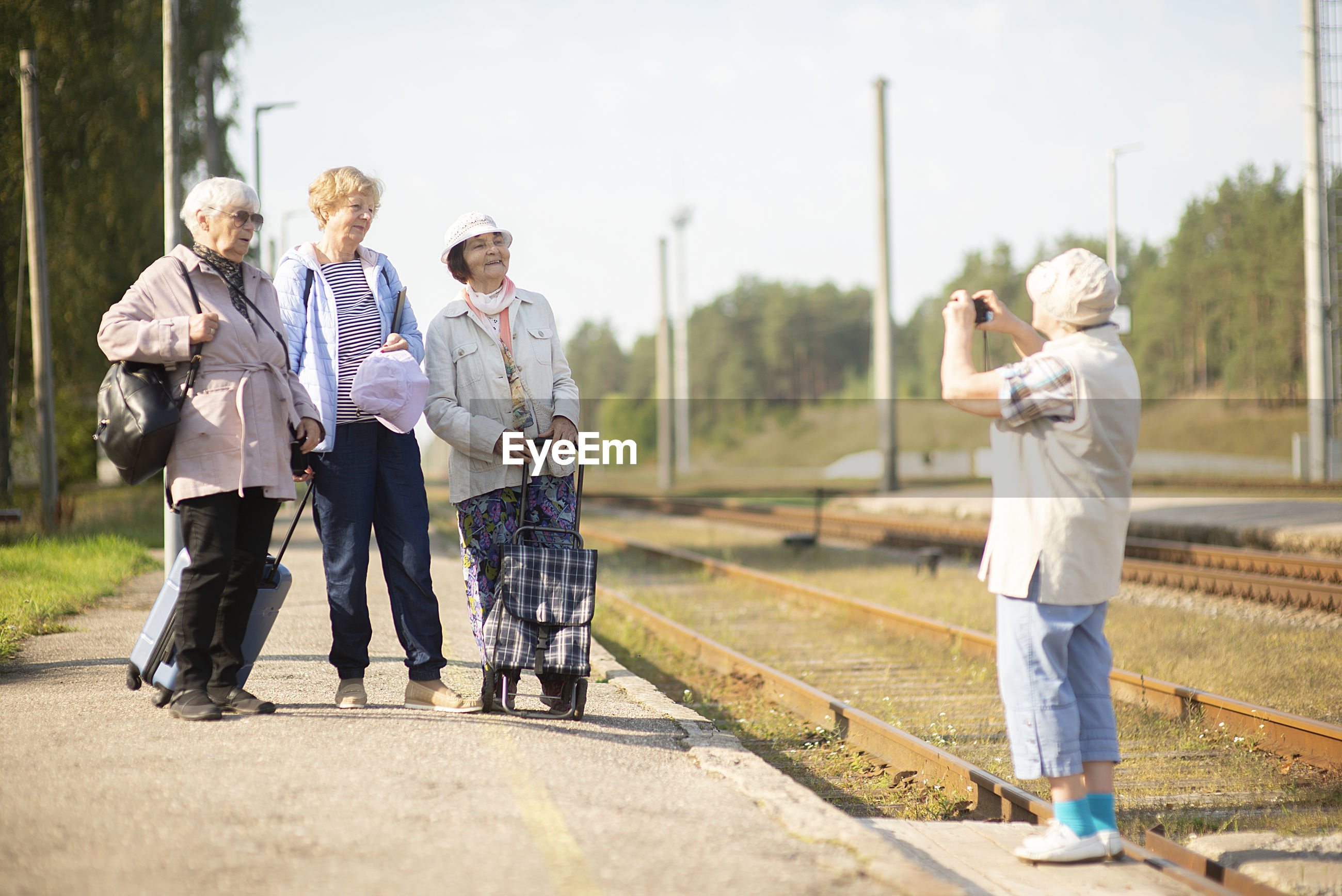 Senior women take a photo on a platform waiting for a train to travel during a covid-19 pandemic