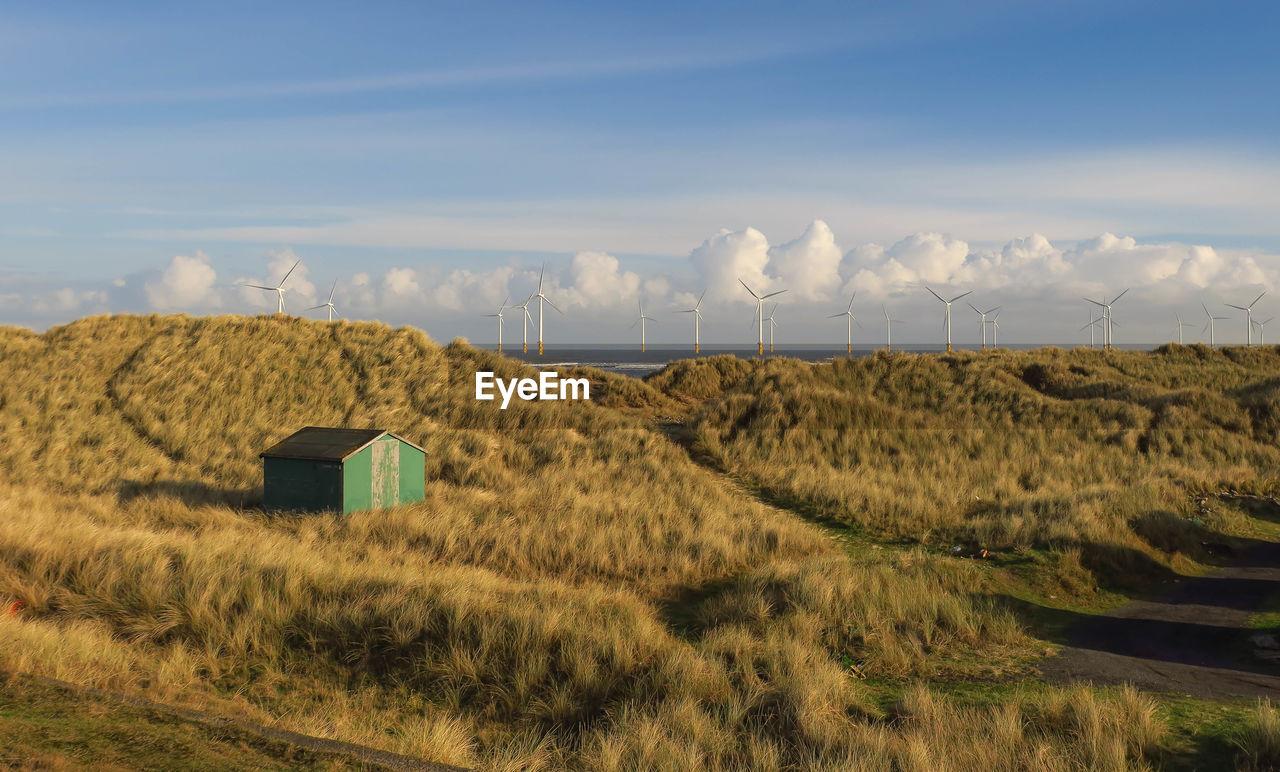 Hut on landscape against sky