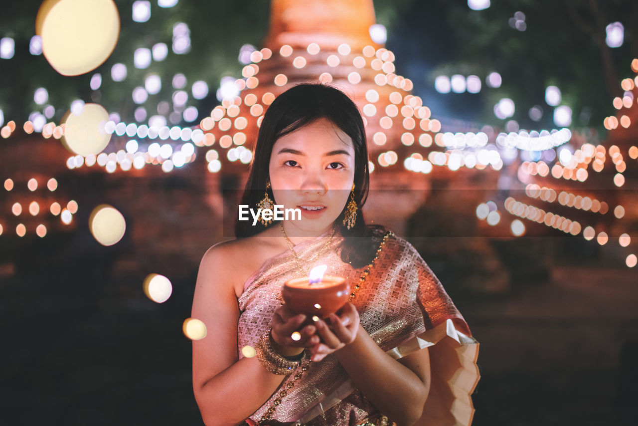 Portrait Of Young Woman Holding Diya While Standing Against Illuminated Temple At Night