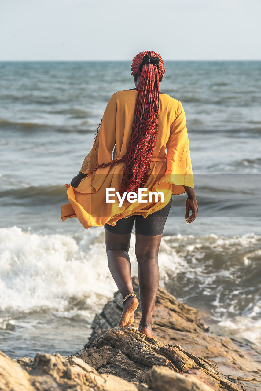 African woman walking on rocks by the beach in accra. has braided red rasta hair, ghana west africa.