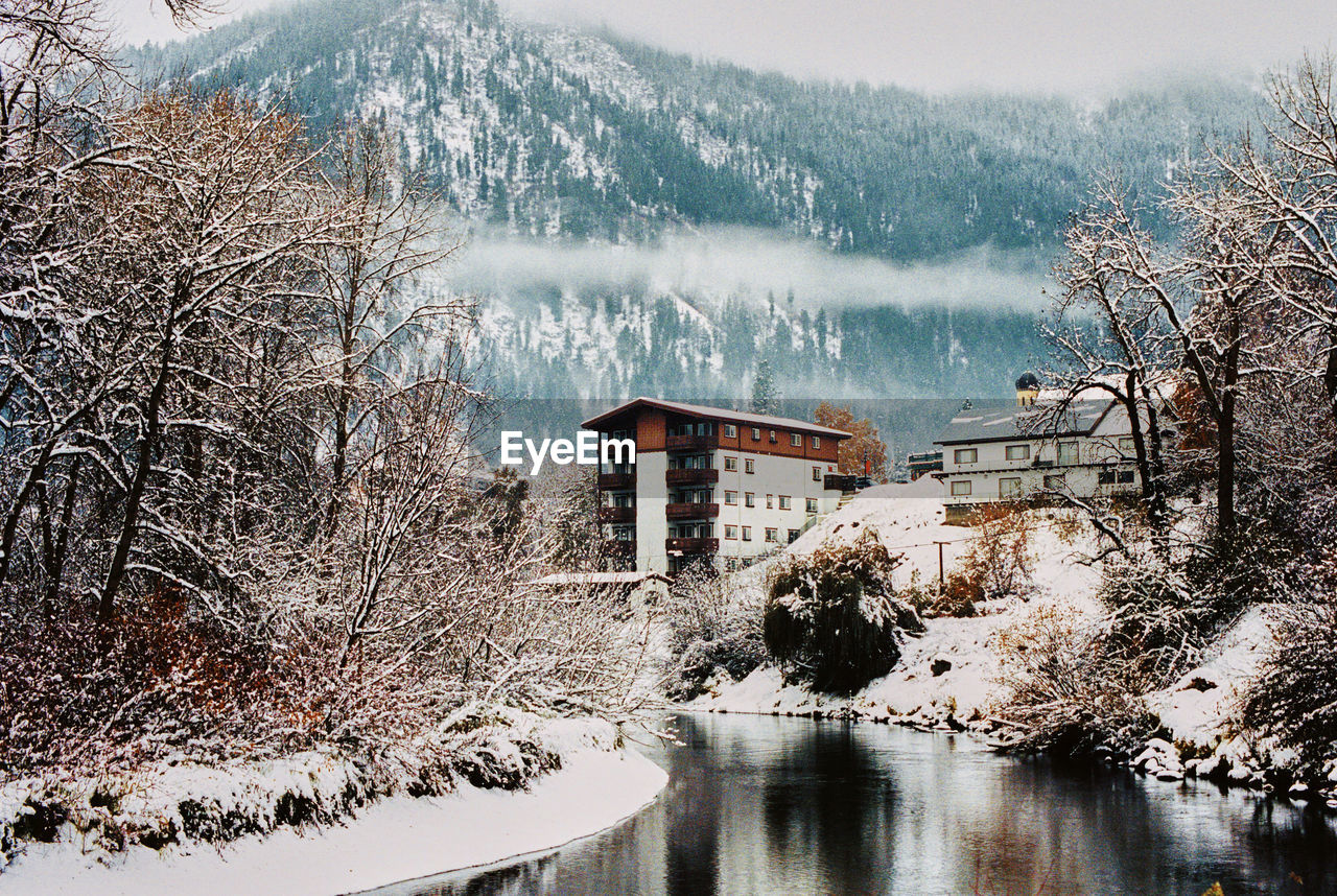 snow, tree, winter, water, nature, architecture, built structure, cold temperature, building exterior, plant, no people, beauty in nature, building, lake, house, day, bare tree, frozen, outdoors, extreme weather, snowing