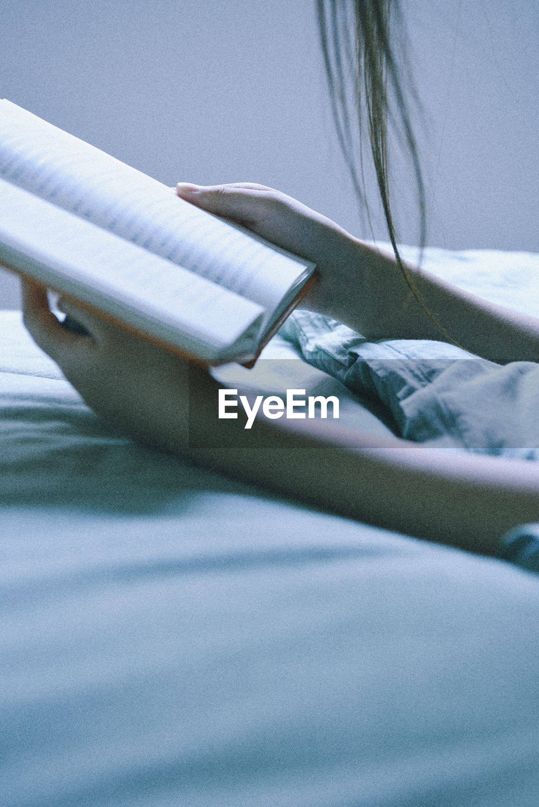 Close-up of woman reading book on bed
