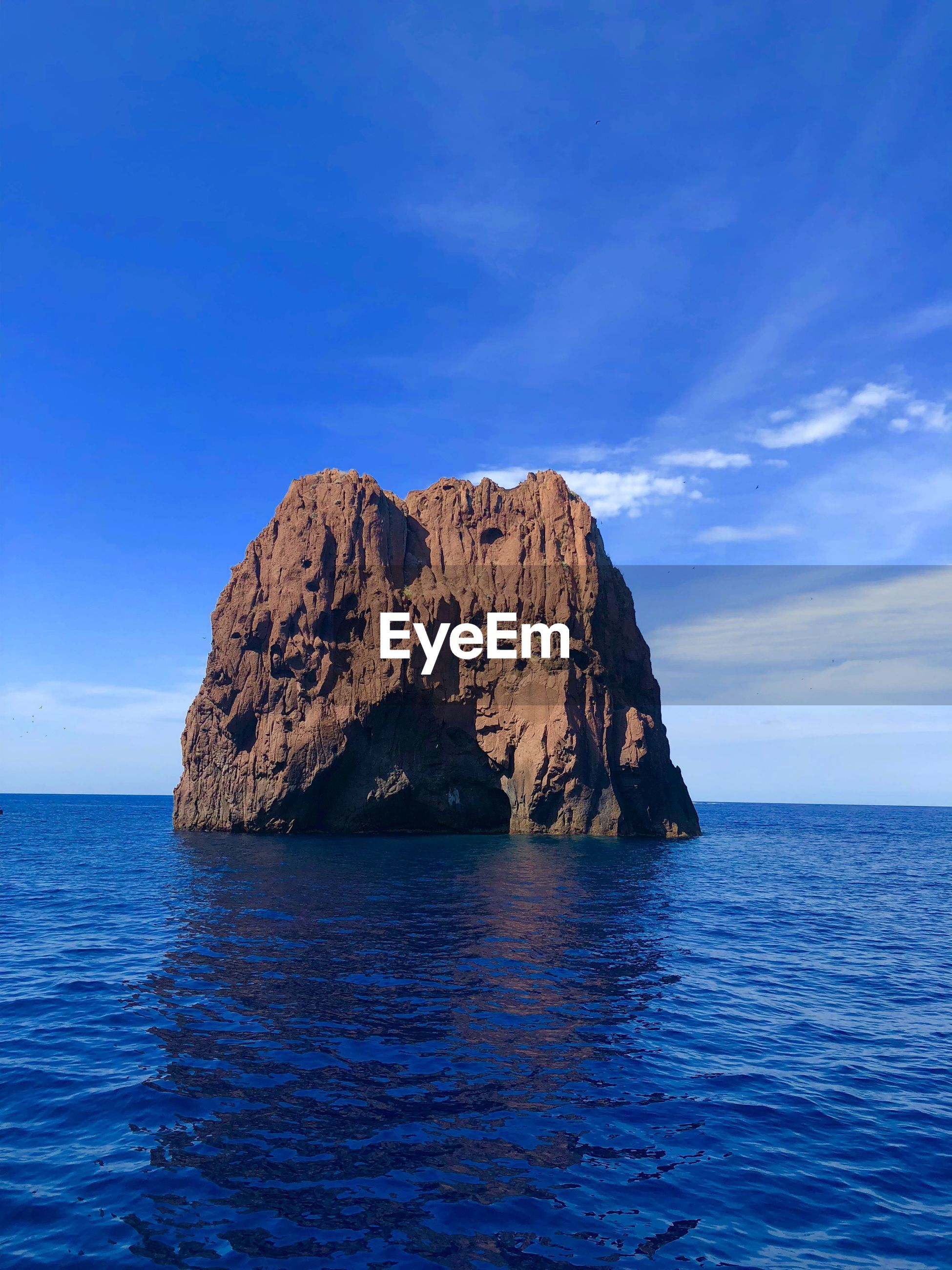 SCENIC VIEW OF ROCK FORMATION IN SEA AGAINST BLUE SKY