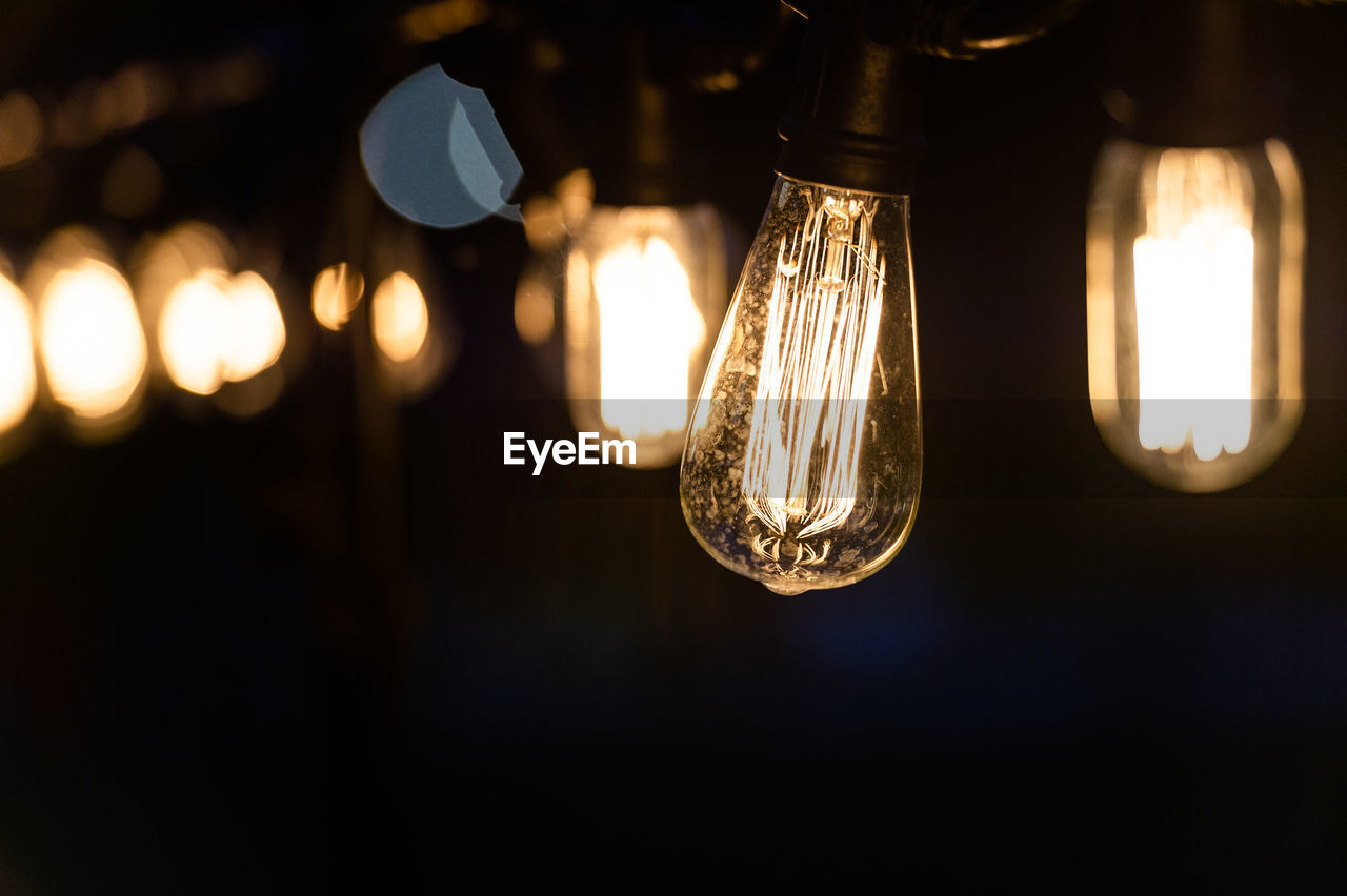 lighting equipment, illuminated, electricity, light bulb, glowing, close-up, light, filament, focus on foreground, no people, electric light, technology, glass - material, transparent, light - natural phenomenon, indoors, hanging, fuel and power generation, night, dark, electrical equipment, power supply, electric lamp