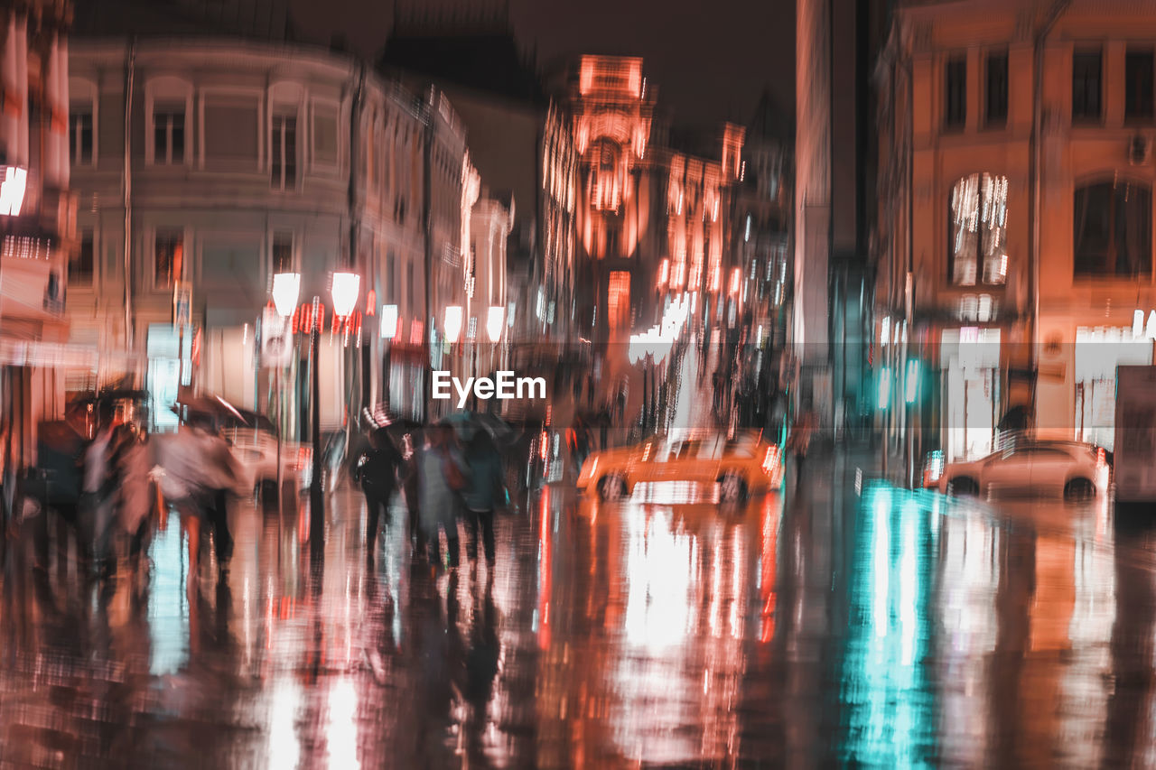 architecture, illuminated, water, city, transportation, reflection, night, built structure, building exterior, group of people, rain, motion, wet, blurred motion, street, walking, city life, real people, rainy season
