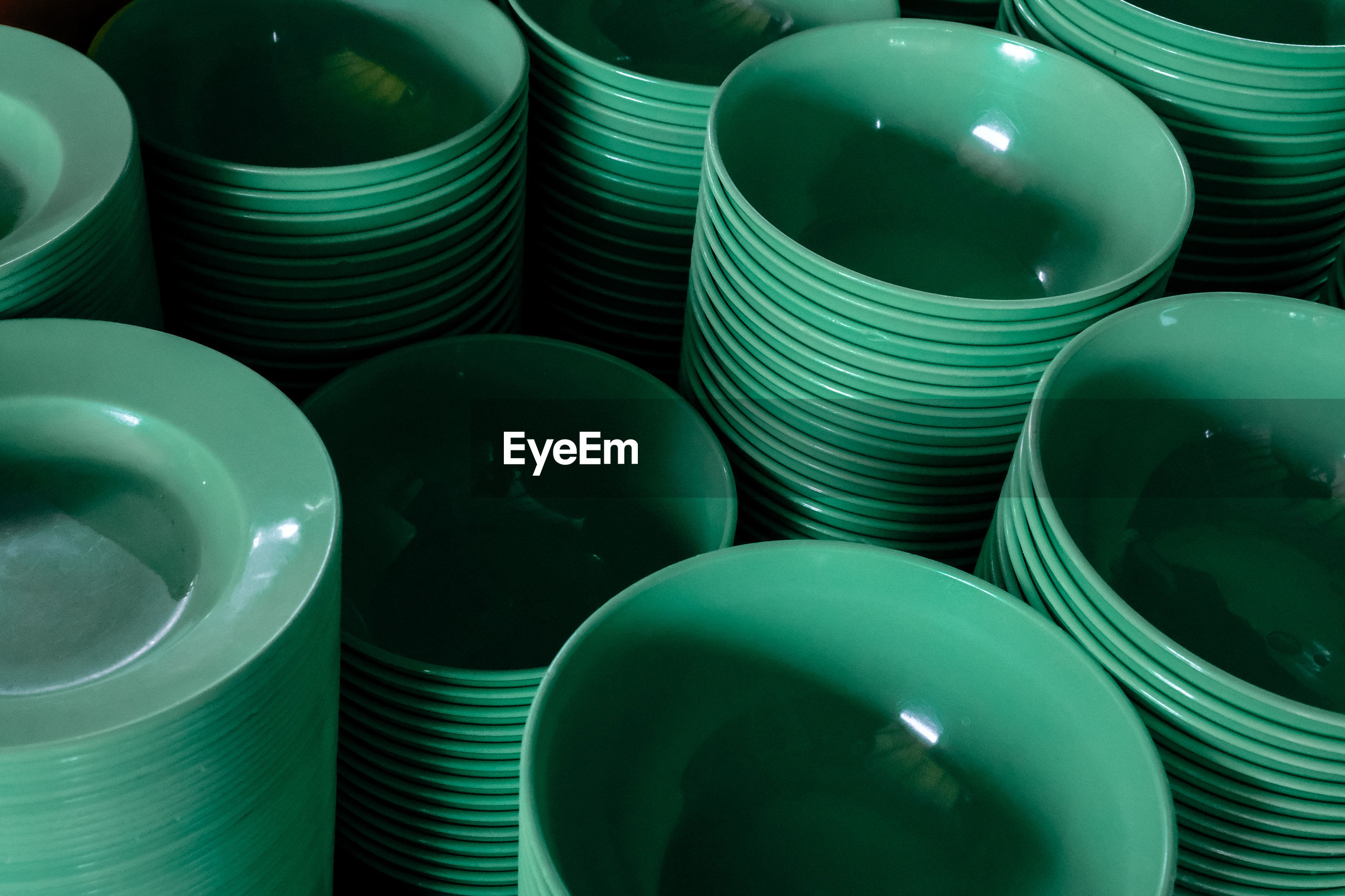 A stack of green plastic bowl