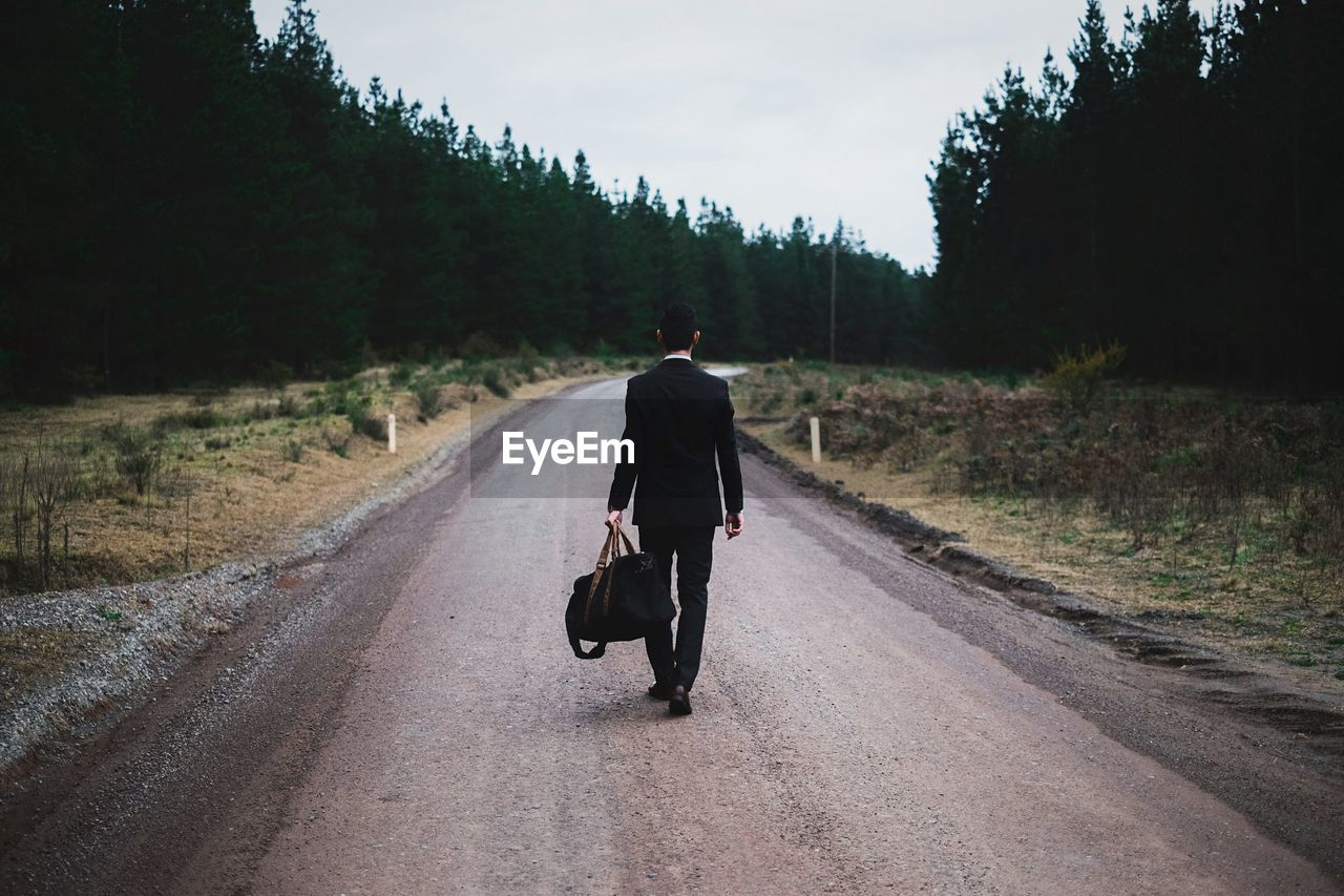 Full length rear view of man with luggage walking on road against sky