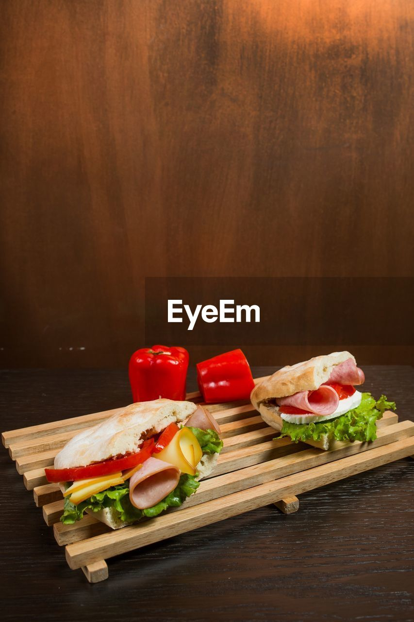 food, food and drink, vegetable, freshness, healthy eating, sandwich, indoors, tomato, wellbeing, bread, wood - material, meal, ready-to-eat, no people, meat, studio shot, lettuce, fruit, still life, cutting board, take out food, snack, bun, tray
