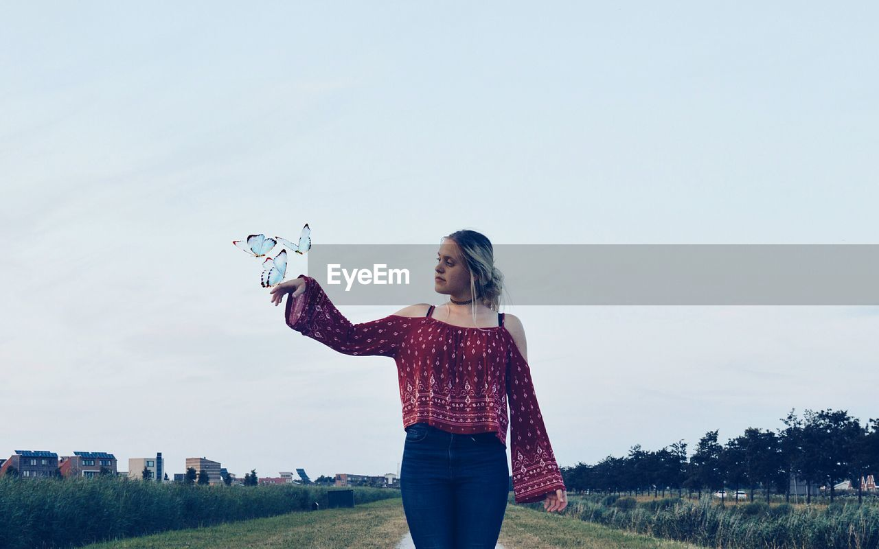 Digital Composite Image Of Butterflies Flying By Woman On Field Against Sky