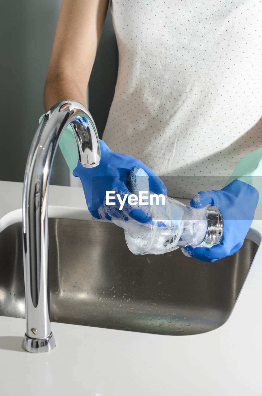 Midsection Of Woman Washing Glasses
