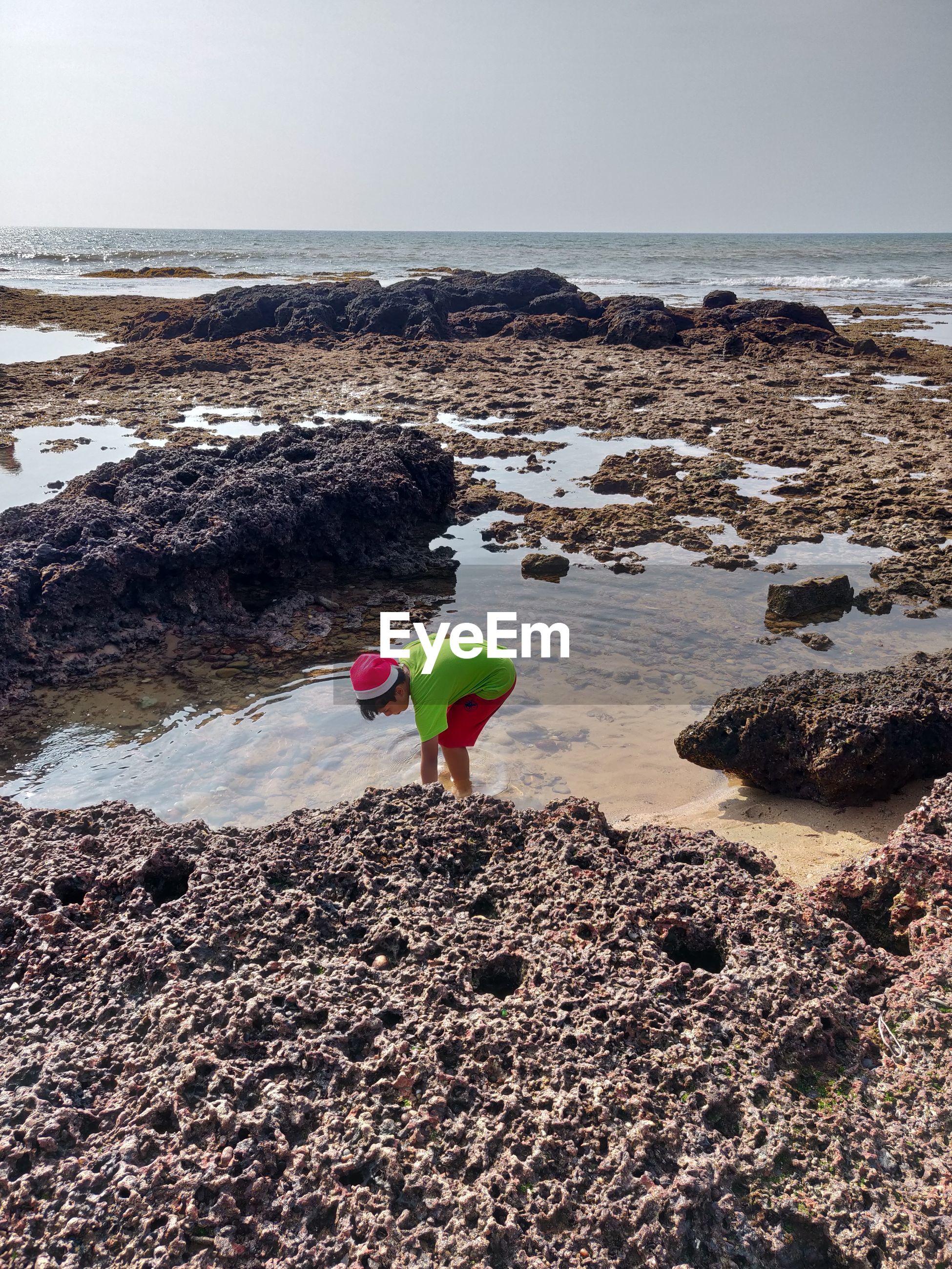 Boy on rock at beach against sky