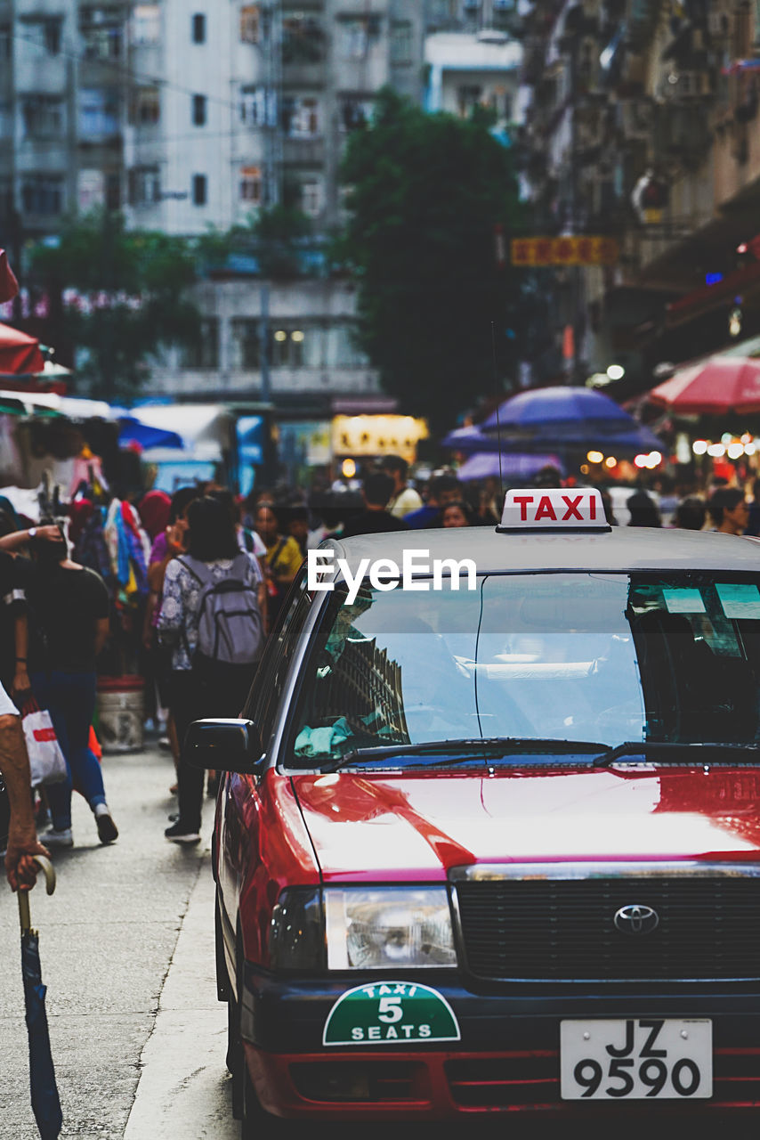 city, street, car, architecture, motor vehicle, transportation, mode of transportation, real people, incidental people, building exterior, land vehicle, built structure, city life, people, city street, men, road, group of people, focus on foreground, outdoors