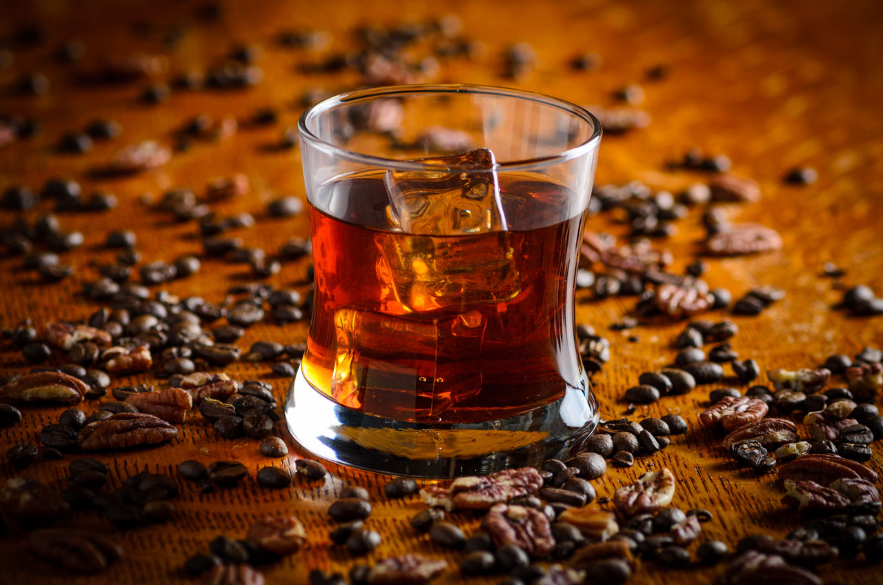 High Angle View Of Whiskey Glass Amidst Scattered Coffee Beans On Table