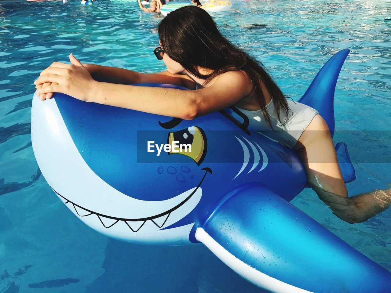 water, swimming pool, real people, leisure activity, inflatable, one person, inflatable ring, vacations, lifestyles, pool raft, young women, young adult, bikini, day, outdoors, full length, blue, swimming, nature, sea, beautiful woman