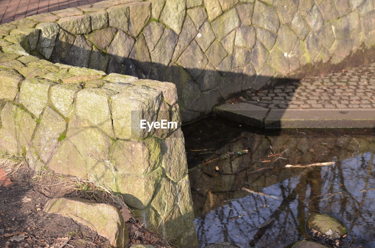 rock - object, day, high angle view, water, built structure, outdoors, no people, architecture, nature, close-up, tiled roof