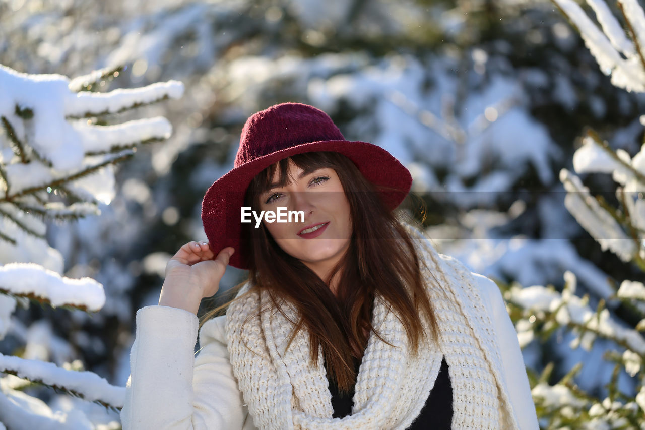 Portrait of young woman against snowy plants during winter