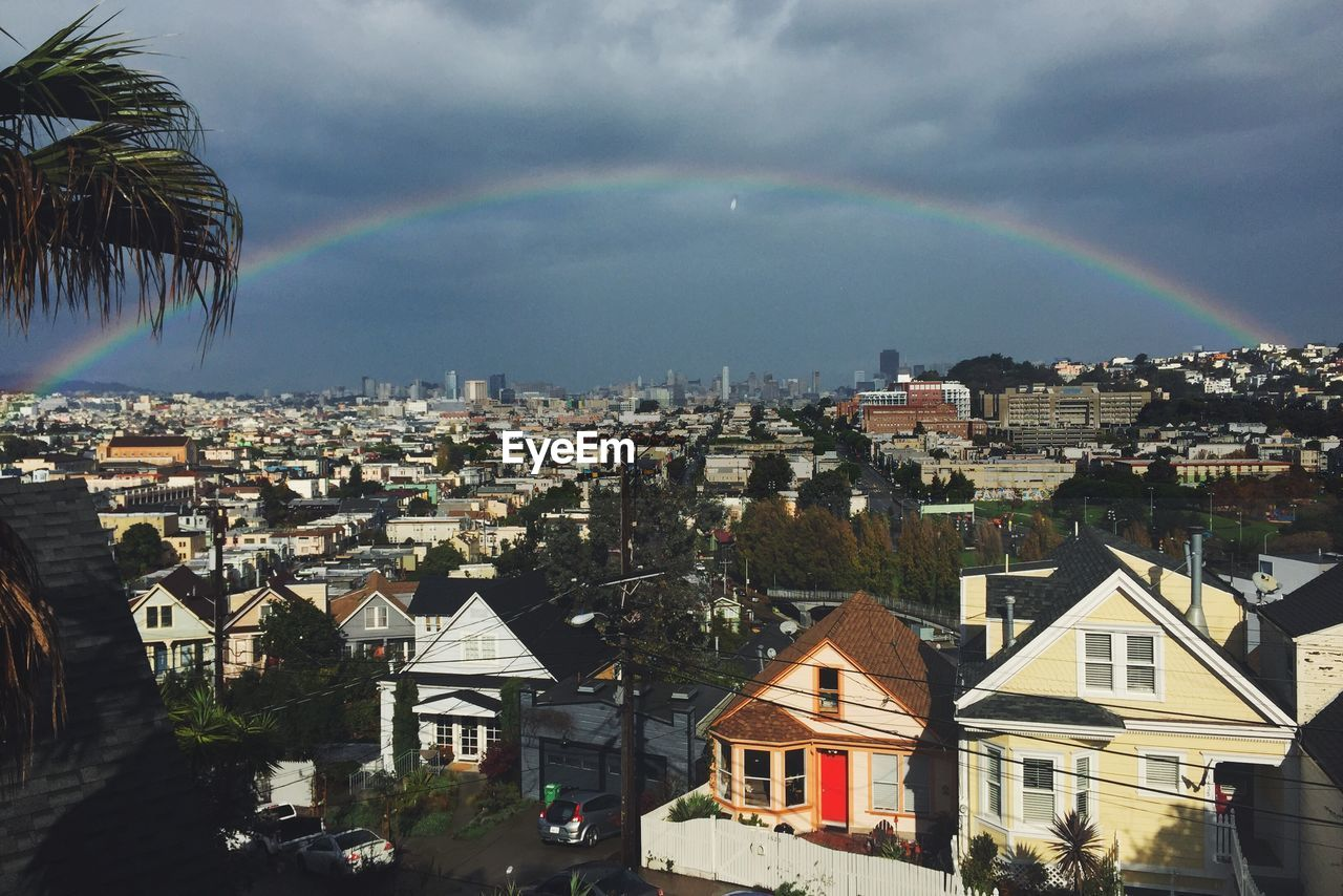 Rainbow Over Residential District Against Cloudy Sky